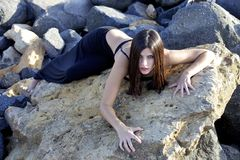 Sensual female model like tiger laying on rocks looking. Sexy female model posing during sunset in exterior Stock Image