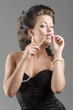 Sensual girl in balck corset. Young and woman in black corset with creative and perfect make up and hair style biting a pearl necklace stock photo