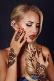 Sensual girl with blond hair with mehendi pattern on hands. Fashion studio photo of beautiful sensual girl with blond hair with mehendi pattern on hands Royalty Free Stock Image
