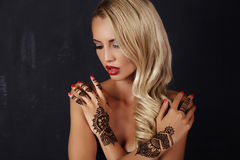 Sensual girl with blond hair with mehendi pattern on hands. Fashion studio photo of beautiful sensual girl with blond hair with mehendi pattern on hands Stock Images