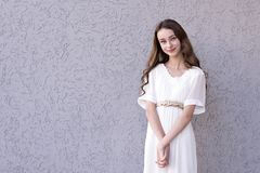Sensual girl with charming appearance. Portrait of happy smiling teenager standing in stylish white dress and looking at camera with gladness. Copy space in left royalty free stock photography
