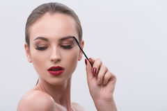 Sensual girl combing her brows carefully Royalty Free Stock Image