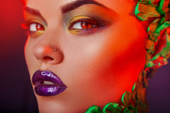 Sensual girl with creative makeup in red lights Stock Photography