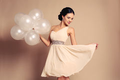 Sensual girl with dark hair in elegant beige dress holding white balloons Royalty Free Stock Images