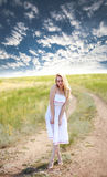 Sensual girl in dress on country road on dramatic sky Stock Images