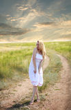 Sensual girl in dress on country road on dramatic sky Stock Photo