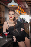 Sensual girl with gorgeous decolletage sitting dreaming at the bar with a drink. Beautiful girl with gorgeous body with makeup. Sensual girl with gorgeous Stock Image