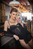 Sensual girl with gorgeous decolletage sitting dreaming at the bar with a drink. Beautiful girl with gorgeous body with makeup Royalty Free Stock Image