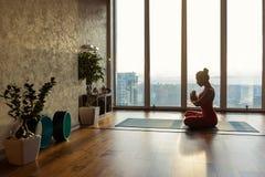 Sensual girl meditating in empty room Stock Photo
