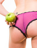 Sensual girl with nice buttocks and apple in hand Royalty Free Stock Photos