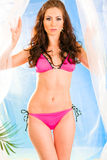 Sensual girl in pink bikini posing on beach. Royalty Free Stock Photos