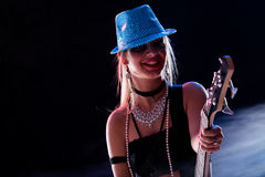 Sensual girl playing on stage. On a dark background as a popstar or rockstar royalty free stock images
