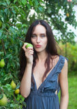 Sensual girl portrait. At yard. Outdoor shot. Pear and eating Royalty Free Stock Photography