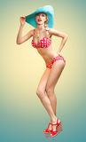 Beautiful woman in red polka dots fashionable swimsuit. PinUp. Playful sexy girl surprised looks, blue hat. Beach body, slim female figure, people, copyspace Stock Photos