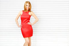 Sensual girl in red dress with beautiful make-up. On light background Royalty Free Stock Images