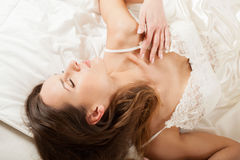 Sensual girl in sexy nightwear lying in bed Stock Photos