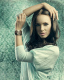 Sensual girl with smooth hair near old fashion wallpapaper. Very pretty young girl posing with brown smooth hair, causal clothes and leather bracelet, looking in Stock Image