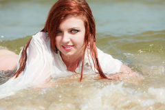 Sensual girl wet cloth in water on the coast. Stock Images