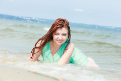 Sensual girl wet cloth in water on the coast. Royalty Free Stock Images