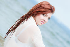 Sensual girl wet cloth in water on the coast. Vacation. Sensual girl wet cloth in water on the coast. Redhair woman having fun relaxing on the sea. Summertime Royalty Free Stock Image