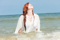 Sensual girl wet cloth in water on the coast. Vacation. Sensual girl wet cloth in water on the coast. Redhair woman having fun relaxing on the sea. Summertime Royalty Free Stock Photography