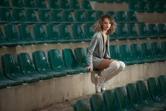 Free Sensual Girl With Long Legs In The Courts Of A Field .Long Legs Attractive Blonde With Curly Hair Relaxing On The Chair Stock Photo - 112964400