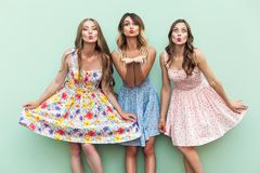 Sensual girls send air kiss at camera with love. Three passion sisters in dress on green background, studio shot Royalty Free Stock Photos