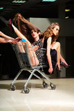 Sensual girls with shopping trolley Royalty Free Stock Photo