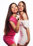 Sensual girls singing with microphone. Two sensual girls singing with microphone, isolated on white Royalty Free Stock Images