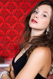 Sensual glamour girl on red vintage background. Inside studio shot Stock Photography