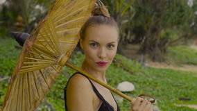 Sensual glamour woman in black bikini with chinese umbrella on a beach. Beautiful blonde glamour woman wearing black swimwear with chinese umbrella smiling and stock video footage