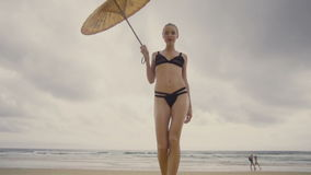 Sensual glamour woman in black bikini with chinese umbrella on a beach. Bottom view of beautiful blonde glamour woman wearing black swimwear with chinese stock video
