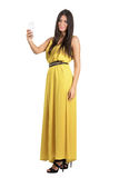 Sensual gorgeous Hispanic woman in yellow jumpsuit taking cellphone selfie with one hand. Full body length portrait isolated over white studio background Royalty Free Stock Photos