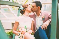 Sensual groom kissing bride on bridge. In garden Stock Image