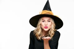 Sensual Halloween Witch Studio Portrait. Attractive young woman dressed in witch halloween costume blowing a kiss towards camera. Sensual Halloween Witch Studio royalty free stock photo