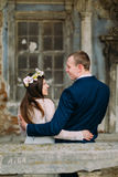 Sensual husband and wife hugging under archway in antique ruined palace. Back view Stock Image