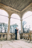 Sensual husband and wife hugging under porch arches in antique ruined palace Stock Photo