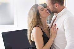 Sensual kiss at work Stock Photography