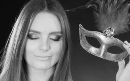 Sensual lady holding carnival mask. Sensuality celebrations people concept. Sensual lady holding carnival mask. Young woman has amazing and delicate make up Stock Images