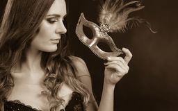 Sensual lady holding carnival mask. Sensuality celebrations people concept. Sensual lady holding carnival mask. Young woman has amazing and delicate make up Royalty Free Stock Image