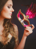 Sensual lady holding carnival mask. Sensuality celebrations people concept. Sensual lady holding carnival mask. Young woman has amazing and delicate make up Royalty Free Stock Photos