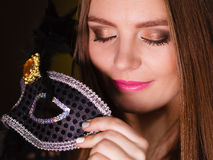 Sensual lady holding carnival mask. Sensuality celebrations people concept. Sensual lady holding carnival mask. Young woman has amazing and delicate make up Stock Photo