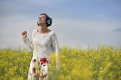 Sensual lady listening to music in headphones and dancing in a cano Stock Photos