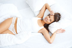 Sensual lady relaxing on white bed Stock Images