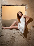 Sensual lady in white dress looking to the window and red sun behind her Royalty Free Stock Photos