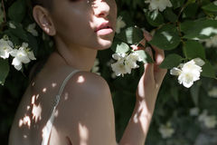 Sensual lips of a beautiful girl in jasmine flowers royalty free stock photography