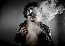 Sensual male biker with sunglasses era dressed Leather jacket, h. Uge smoke over dark background Stock Images