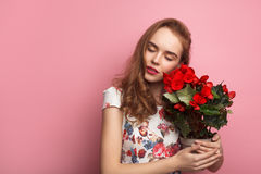 Sensual model with flowerpot. Young stylish girl in dress holding flowerpot keeping eyes closed on pink royalty free stock image