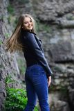Sensual model with makeup after hairdresser. girl in casual clothes outdoor. look of girl near stony wall. woman stock image