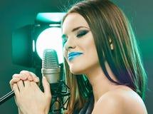 Sensual modelo bonito que canta em um microfone Imagem de Stock Royalty Free